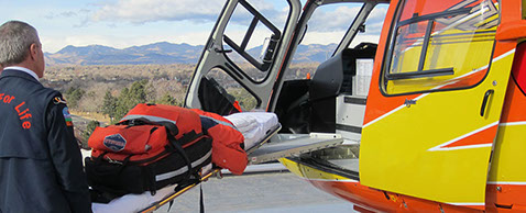 Emergency medical technician placing equipment in helicopter for user testing, market analysis, and usability testing